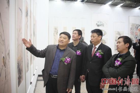 著名国画家谢登科(左)向领导和嘉宾讲述李俊香国画作品的艺术特色 中国经济网记者李冬阳摄